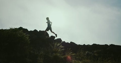 Athletic man trail running in foggy mountains