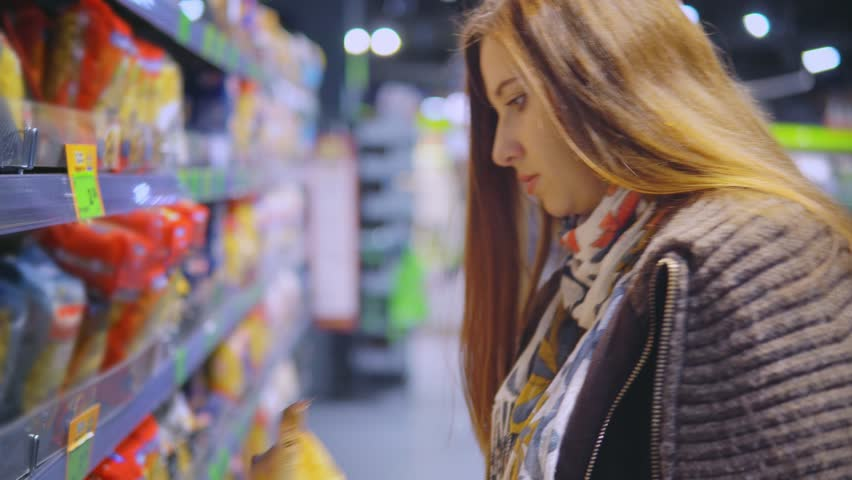 A woman is buying macaroni in a store. | Shutterstock HD Video #32953063