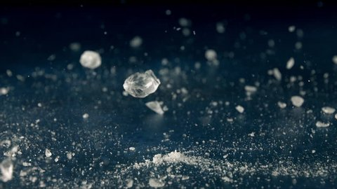 Ice cube bouncing and crashing on blue sheet with dark background table top in slow motion