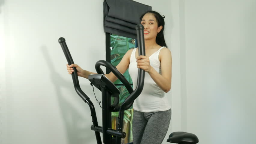 4k of Active young woman working out on exercise bike stationary bicycle. Sporty girl training at home. Fitness and weight loss concept. | Shutterstock HD Video #32982343