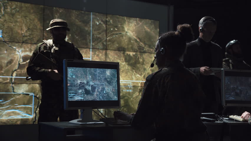 Group of young male and female soldiers in headphones and on computers in communications center coordinating and launching a missile | Shutterstock HD Video #32991094