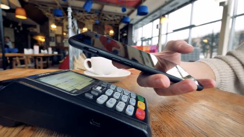 Smartphone payment. Female hand pay using nfc system and contactless card.