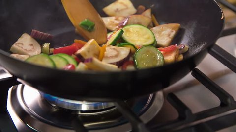 Cooking healthy and organic vegetables in a wok. Cook is turning wok with special movements so vegetables flip.
