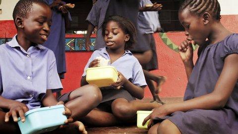 4k of African school children eating packed lunch at playtime break.