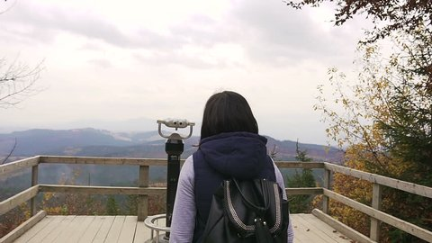 Girl viewing horizon. A young girl tourist with dark backpack fits to the binoculars standing on the observation deck in the mountains. Binocular on the mountain, coin operated binocular slow motion