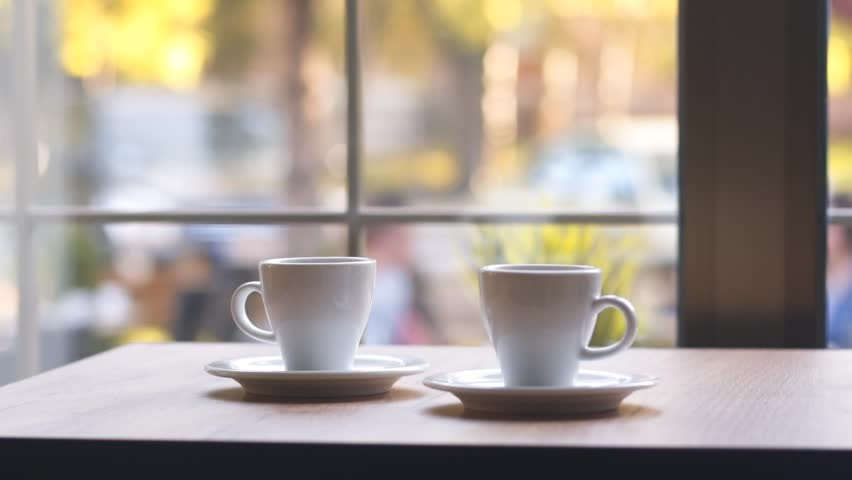 SLOW MOTION: Two cups of espresso coffee on a wooden table indoors. Morning coffee, morning ritual. Coffee for two at home by the window. | Shutterstock HD Video #33013666