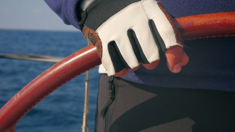 Closeup on skippers hand wearing gloves and turning steering wheel. Keeping sailing boat in right direction so sails can catch lots of wind. Filmed in slow motion hd.