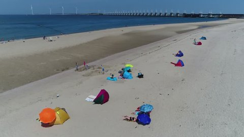 Aerial over summertime beach showing people recreating on sand using colorful parasols beach towels in background showing Oosterscheldekering Eastern Scheldt storm surge barrier part of Delta Works 4k