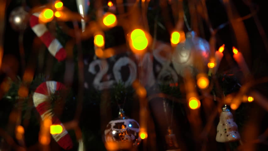 Plate numbered 2018 on a Christmas tree among toys and yellow electric lights, New Year's background. | Shutterstock HD Video #33030628