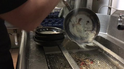Restaurant dishwasher sprays out saute pans before setting them into holding area for subsequent cleaning.