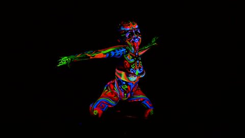 Beautiful young sexy girl in lingerie dancing with ultraviolet paint on her body. Girl with neon bodyart in color light.