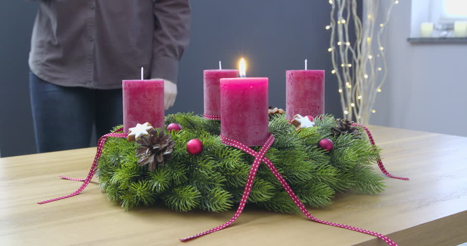 Second Sunday of Advent - a young woman is lighting the second candle of the advent wreath