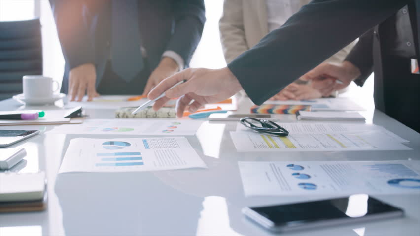 Business team sharing ideas about the financial development of their company. They are discussing over financial data and graphs. | Shutterstock HD Video #33072133