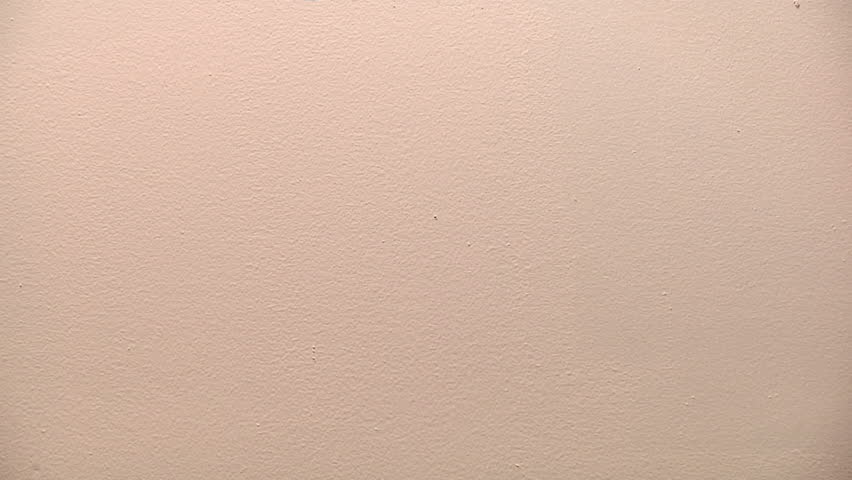 painter rolls red paint onto a white wall