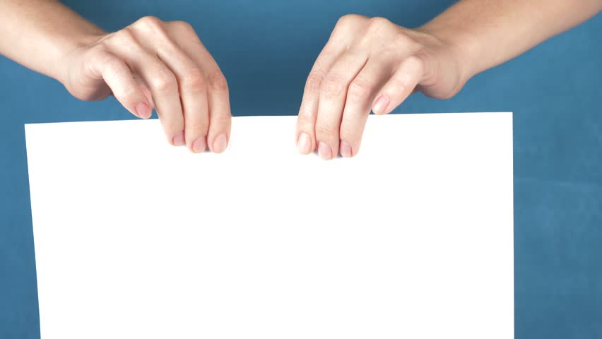 Hands tearing paper sheet, closeup on a turquoise background. 4k, slow motion   Shutterstock HD Video #33079006