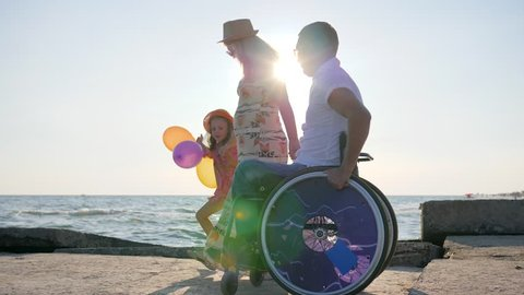 kid at holiday on Sea together with disabled parents, invalid in wheelchair walks with wife and daughter