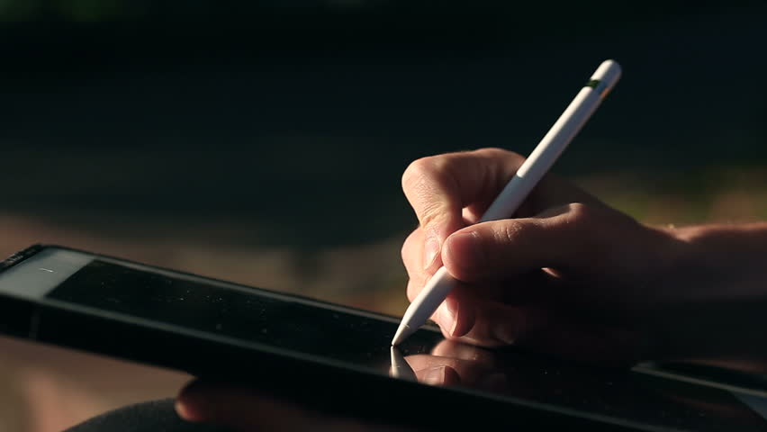 Extremely closeup shot of painter's hand drawing a sketch on tablet using stylus at park.  | Shutterstock HD Video #33082768