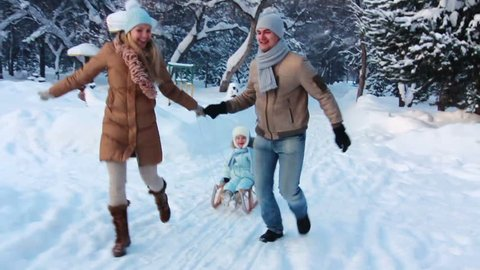 Portrait of young parents running, with their child on a sled in the winter park. Family in winter scene holding hands and smiling.