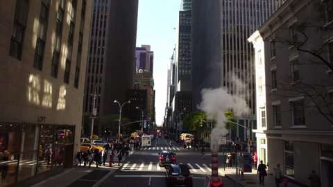 New York City, NY - SEPTEMBER 17, 2017:  Drone shot of busy NYC New York City Manhattan street with steam during the day. Busy iconic street with skyscrapers in Manhattan in NYC.