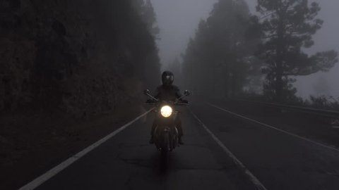 Moto ride in the morning in the woods, fog, mist low visibility rainy ride in the clouds. Scenic oldschool motobike Triumph riding in the mountains.