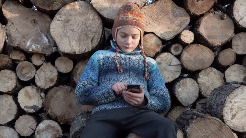The boy is playing on the smartphone and hiding it behind his back. Portrait of a child on the background of firewood playing on a smartphone.  | Shutterstock HD Video #33094120