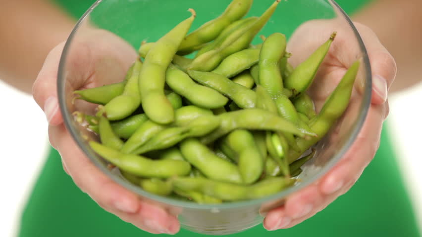 Soy beans - healthy food. Woman showing healthy green fresh edamame bean.soya beans in closeup.