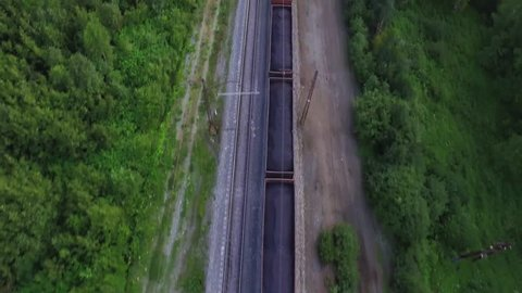 Freight train carries with coal an electric locomotive by two-sided Trans Siberian railway in Ural Mountains - Aerial Photography, top view