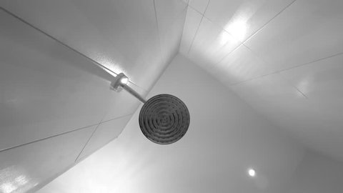 Shower head in bathroom. Falling water drops. Black and white.