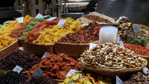 Large Counter of Dried Fruits and Nuts at a Farmers Market in La Boqueria. Barcelona. Spain. Nuts, dry fruits on display at the market on the showcase. Stall with Various dried fruits at Mercat de