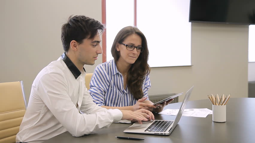 In office woman with tablet and man working in front of laptop. Young guy and lady with glasses are smiling and pointing at monitor screen with their fingers. | Shutterstock HD Video #33158443