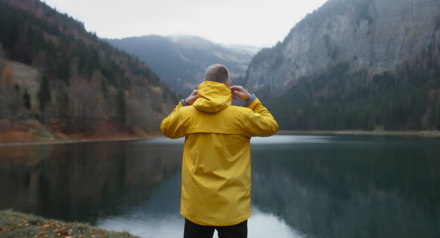 Back view of Caucasian male hiker in yellow raincoat stands near beautiful lake in Alps, rainy weather, morning shot. 4K UHD 60 FPS SLO MO
