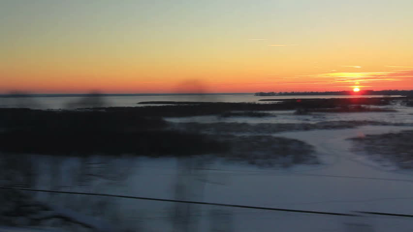 Views high-speed train to the forest and the frozen lake at sunset