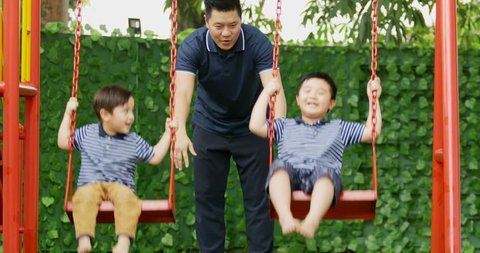Happy young father pushing his sons on swing at the park, shot in 4k resolution