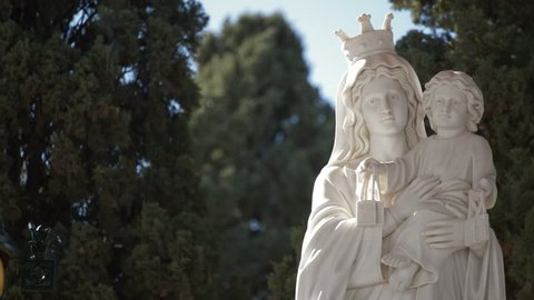 Statue of virgin mary crowned with child in arms a sunny day