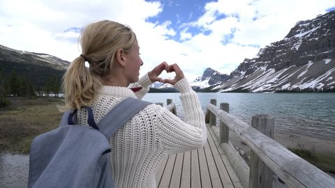 4K video of young woman by the mountain lake making a heart shape finger frame on the beautiful landscape. People love nature environment travel concept Shot in Banff national park, Alberta, Canada