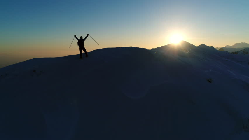 Aerial - Flyover silhouette of adult male mountaineer with trekking poles that raises arms on top of snowy mountain after successful climb in winter season | Shutterstock HD Video #33212986