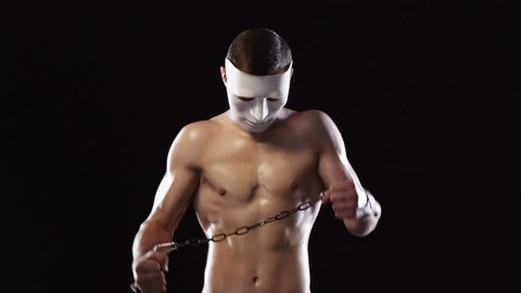 Strong athletic man with muscular torso wearing white mask with hands in handcuffs tied breaking chain