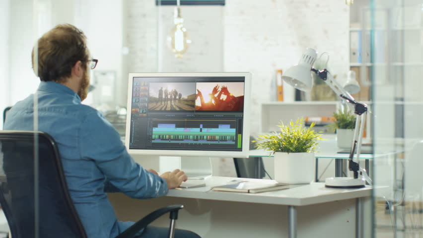 Male Video Editor Works with Footage and Sound on His Personal Computer with Two Displays. He Works in a Bright Office Loft. Shot on RED EPIC-W 8K Helium Cinema Camera.