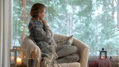 Cozy winter lifestyle. Young happy woman drinking cup of coffee wearing knitted sweater sitting home by the big window with winter snow tree background. Slow motion