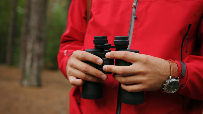 Close up of the appealing young man rising his hands with binoculars and looking in the binoculars in the forest. Outside. Portrait