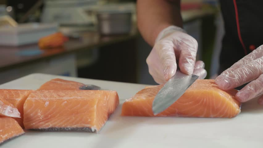 Close-up of sushi chef in gloves slices fresh salmon at sushi bar. Professional cook cutting fish fillet at commercial kitchen, slow motion.