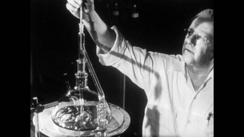 1940s: Male scientists stand in laboratory. Beakers and flasks bubble and boil. Scientists adjust instruments. Liquid pours out of chute. Smoke pours out of factory chimneys.