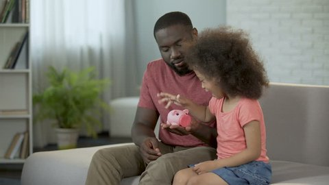 Caring father teaching child to save money, putting coins into piggy bank