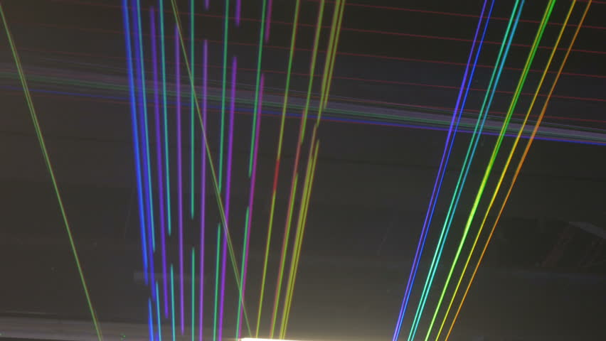 Thin different colored streaks of laser lights expand and collapse while criss-crossing each other.