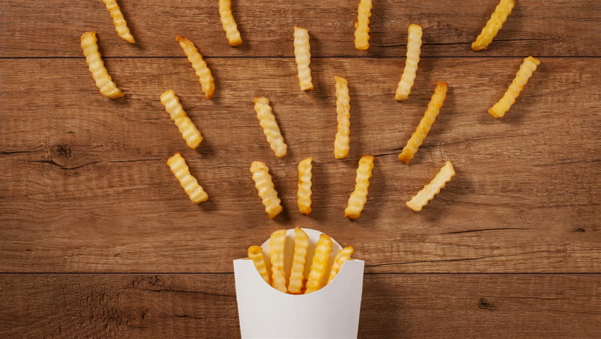 French fries falling into and pouring out of paper holder on brown wooden table - stop motion animation
