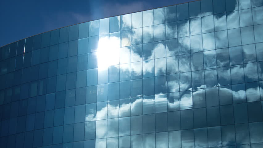 Clouds refelected in modern office building. Zoom and panning.