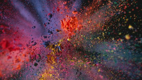 Multi colored powder flying in slow motion as camera pulls away and rotates, shot with high speed motion control.