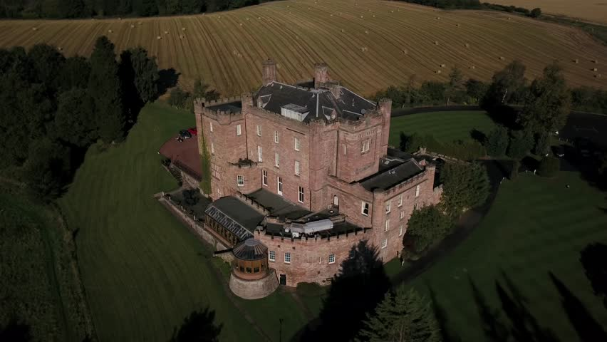 Aerial image of Dalhousie Caslte -Scotland's oldest inhabited castle. It is opened to public. The video shot in early morning with the sun highlighting the building.