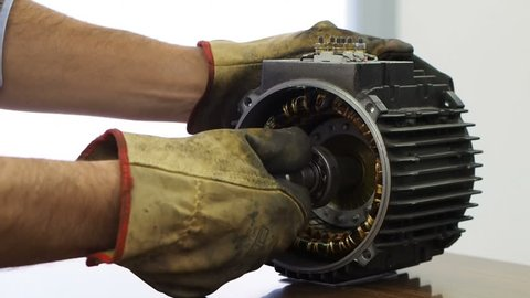 A worker wearing yellow gloves disassembles an electric motor by pulling  out the rotor from the stator