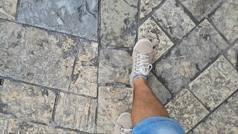 Legs of a male wearing yellow sneakers and short jeans as walking on the street or pavement. First person POV.
